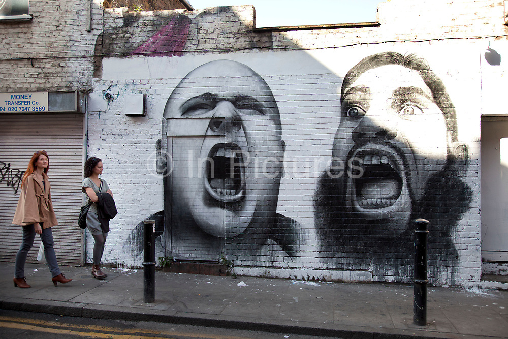 Political mural of two shouting heads off Brick Lane. Street art in the East End of London is an ever changing visual enigma, as the artworks constantly change, as councils clean some walls or new works go up in place of others. While some consider this vandalism or graffiti, these artworks are very popular among local people and visitors alike, as a sense of poignancy remains in the work, many of which have subtle messages.