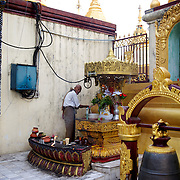 May 09, 2013 - Yangon, Myanmar: A devotee performs a ritual of water offer to a religious statue in a shrine at Sule Pagoda in central Yangon. CREDIT: Paulo Nunes dos Santos