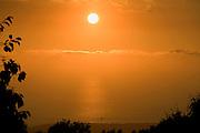 Pacific Ocean sunset with sailboat shot from Kona Palisades Estates, Big Island, Hawaii.