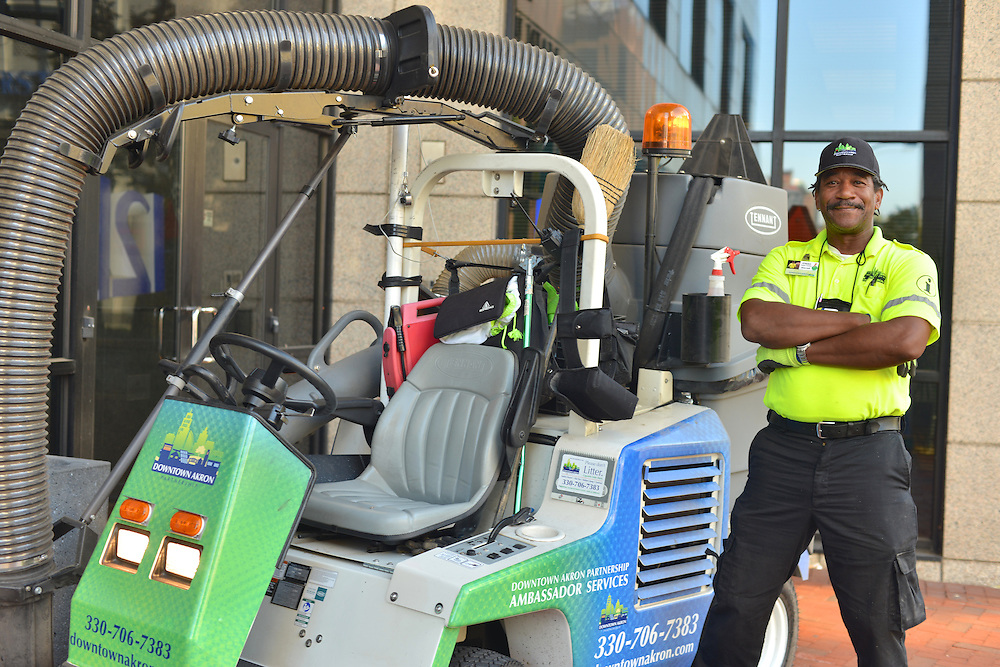A Downtown Akron Partnership cleaning & safety ambassador with a sidewalk sweeper.
