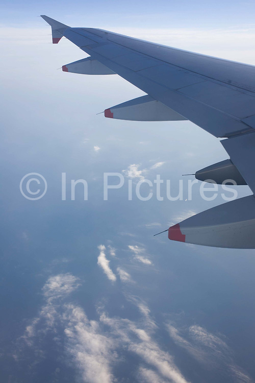 A airliner window seat view of mid-Channel airspace. Clouds and blue sky is seen below and beyong a passenger's commercial aviation experience. From the chapter entitled 'Up in the Air' and from the book 'Risk Wise: Nine Everyday Adventures' by Polly Morland (Allianz, The School of Life, Profile Books, 2015).