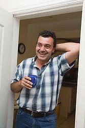 Bulgarian man standing in doorway with a cup of tea,