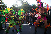 Children taking part in the procession dressed in green are lead and directed by a female dancer dressed in red in East London, United Kingdom,Sept 11 2016. The annual Hackney Carnival took place on a hot summers day and the procession of dancers dressed in various outfits moved through the streets to much joy of the many bystanders.