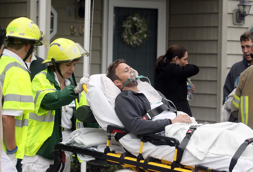 April 06, 2012; Virginia Beach, VA, USA; A man is brought away by paramedics at the scene of a F-18 crash. Mandatory Credit: Peter J. Casey