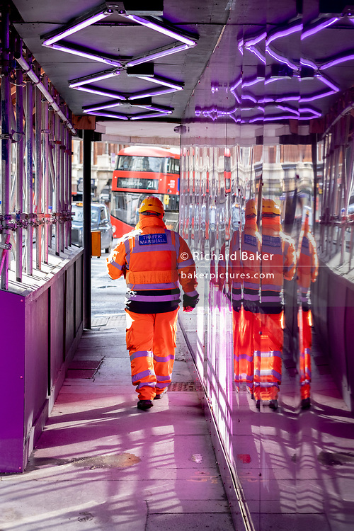 A rear view of an industry Traffic Marshall who walks through a covered pavement where a large construction project is underway on Victoria Street in Victoria, Westminster, on 19th February 2021, in London, England.