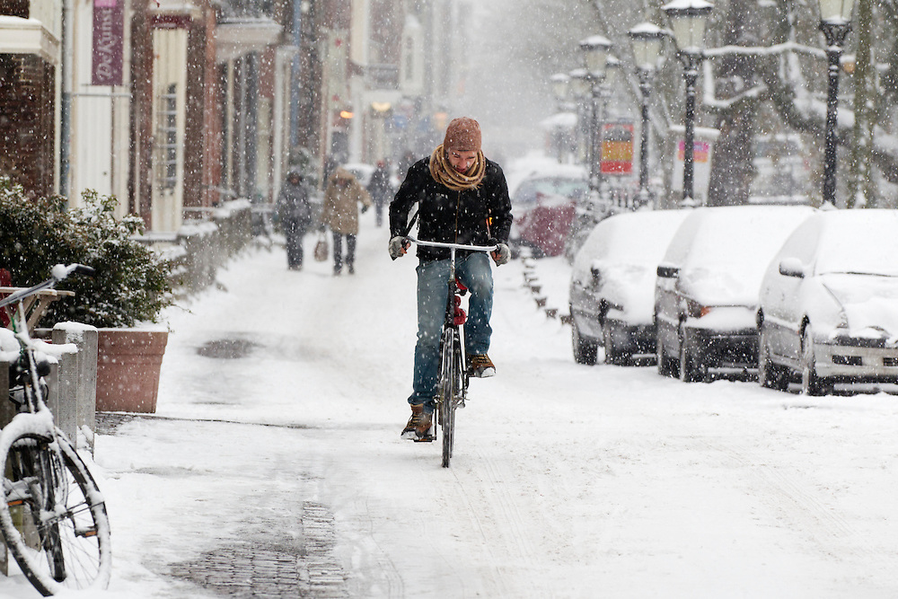 Een jongen probeert zich met de fiets een weg te banen over de Oudegracht in Utrecht in de sneeuw.<br /> <br /> A man is cycling at the Oudegracht Utrecht in the snow