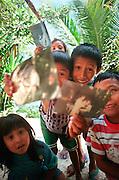 Mayan children smiling holding photographs up to camera - San Jose Guatemala.