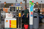 As the fuel crisis in the UK continues, this G4S ambulance driver returns to his vehicle past empty pumps after refuelling at a Shell petrol station on the 1st of October 2021 in Folkestone, United Kingdom. Almost all the petrol stations in Folkestone have no fuel, this Shell garage took a delivery recently and now has queues over half a mile in both directions. People have been waiting for more than 2 hours to get fuel. Panic buying and long queues outside some petrol stations as the crisis, which has been caused by a lack of HGV drivers available to deliver supplies, continues.