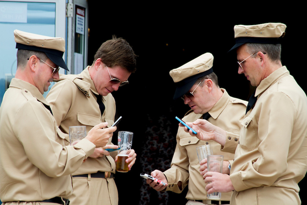 A group of 'GIs' check their smartphones. Each year the South Wales seaside town of Porthcawl is home to the Elvis Festival