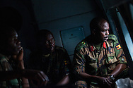 Force commander Col. Joseph Balikuddembe and his intelligence officer stares out the window of an airforce helicopter en route to a remote operating base in Central Africa Republic. Col. Malkiuddembe is leading a grinding effort to eliminate the LRA and capture LRA leader Joseph Kony. Although the UPDF has been chasing Kony for decades, renewed international interest and increased funding from the US have brought the most pressure on Joseph Kony in decades.