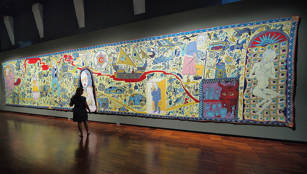"""VENICE, ITALY - JUNE 16: A woman admires """"The Wolthamstow Tapestry 2009"""" a 15mt long tapestry by Grayson Perry on June 16, 2011 in Venice, Italy.Penelope's Labour: Weaving Words and Images, is an exhibition of antique and contemporary tapestries and carpets, curated by Adam Lowe and Jerry Brotton and will stay open until September 18."""