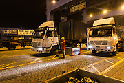 Trucks carrying shipping containers unload their payload at a dock onto CMA CGM SAs Benjamin Franklin container ship at the Xiamen Songyu Container Terminal at night in Xiamen, China, on Saturday, Jan. 30, 2016. The Benjamin Franklin is the largest container ship ever to have docked at a U.S. port.
