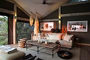 A low sun illuminates the lounge at Abu Camp, a luxury safari camp in the Okavango Delta, Botswana