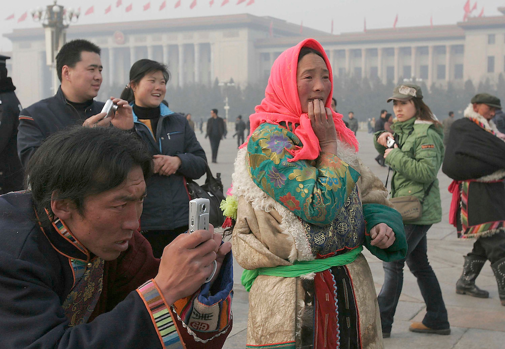 A father from western  China frames a photo of his child at Tiananmen Square with the Forbidden City in the background in Beijing, China.