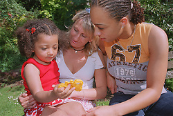 Lesbian couple sitting outside in park with young daughter,
