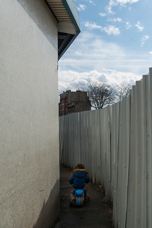 A child rides his bicycle inside a passageway between the social housing complex of Fosses-Jean and the new neighborhood's leisure center construction site, Colombes, France, April 2016.