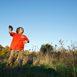 A nine year old boy plays with a football in a field at Elmwood Farm in Hopkinton, Massachusetts. Fall.