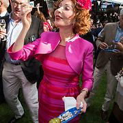 NLD/Amsterdam/20140612 - Hilton Haringparty 2014, Marijke Helwegen hapt van een Hollandse nieuwe haring