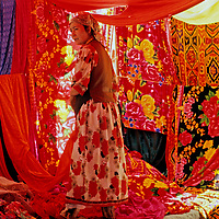 A Uygar woman sells brightly colored fabric in a bazaar near Kashgar (Kashi), a city on the ancient Silk Road in Xinjiang, China.
