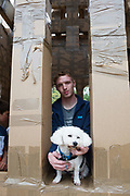 20/07/2018 repro free:  How much is that doggiie in the window.... Sweeney dog from Lackagh with human Jack Taylor  at The People Build at Galway International Arts Festival will see hundreds of volunteers, and the general public, create two large-scale and highly ambitious structures solely from cardboard. Under the guidance of artist Olivier Grossetete and his team, the public will transform thousands of cardboard boxes into a structure to replicate St. Nicholas' Church in Galway. It is being constructed on Eyre Square in Galway today. On Sunday July 22 at 6pm the public will join forces in a massive celebratory demolition, which will see the cardboard building come tumbling down. <br /> <br /> A second structure will consist of a cardboard bridge being built at Waterside in Galway. It will be floated on the water, serving as a testimony to Galway's River Corrib Viaduct, once part of the famous Galway to Clifden Railway. The build will take place on Saturday July 21 and will be demolished on Sunday July 22 at 3pm. <br />  . Photo:Andrew Downes, XPOSURE
