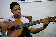 A young Egyptian boy plays an acoustic guitar at the American-sponsored Theban Mapping Project Library on the West Bank of Luxor, Nile Valley, Egypt. He has been playing for only three months and can already play a variety of chords and even recite the theme of the film, Titanic. The Theban Mapping Project's goal is to enable local people to have a place where they can read and learn as state schools are under-resourced, lacking basic teaching aides such as books or musical instruments. The organisation is run by American Egyptologist Dr Kent Weeks who is committed to the original goal of accurately documenting the archaeological heritage of Thebes. (Photo by Richard Baker / In Pictures via Getty Image).