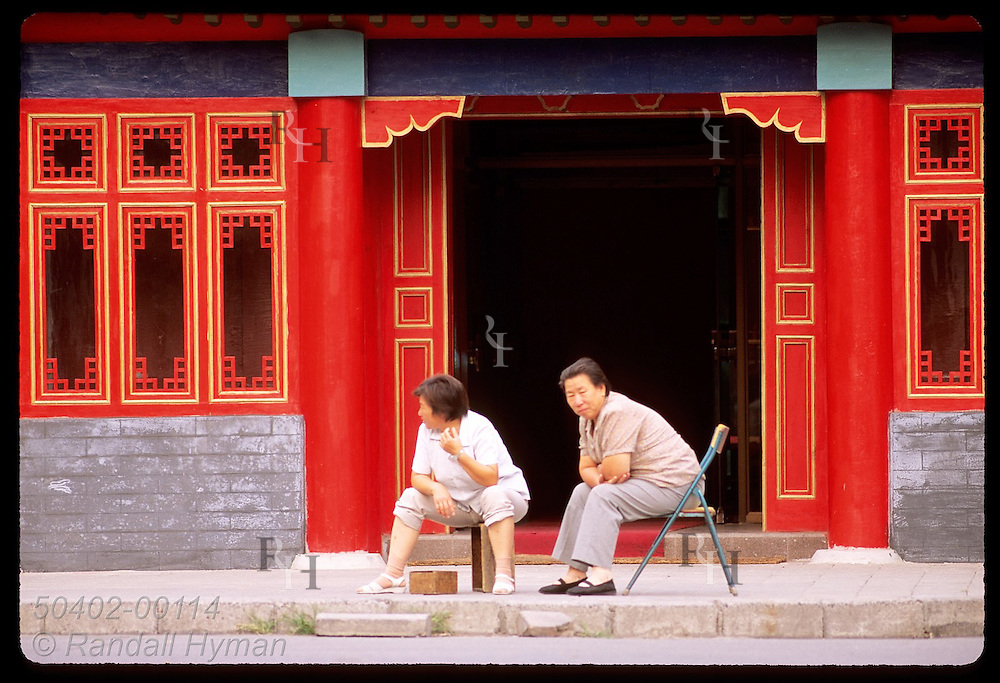Two older women sit before red-and-gold building facade outside the Forbidden City in Beijing. China