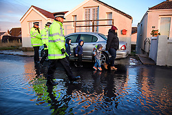 © Licensed to London News Pictures. 13/01/2017. Jaywick, UK. A police officer accompanies a woman and her young children along the seafront at Jaywick, Essex, where homes were expected to evacuated due to the threat of flooding in low-lying areas . Photo credit: Ben Cawthra/LNP