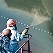two shipyard workers spray painting a ship green in Dubai