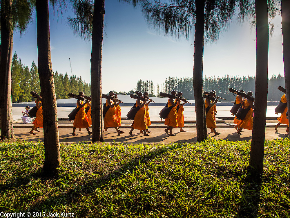 """02 JANUARY 2015 - KHLONG LUANG, PATHUM THANI, THAILAND: Buddhist monks walk through the grounds at Wat Phra Dhammakaya on their way to start the 4th annual Dhammachai Dhutanaga (a dhutanga is a """"wandering"""" and translated as pilgrimage). More than 1,100 monks are participating in a 450 kilometer (280 miles) long pilgrimage, which is going through six provinces in central Thailand. The purpose of the pilgrimage is to pay homage to the Buddha, preserve Buddhist culture, welcome the new year, and """"develop virtuous Buddhist youth leaders."""" Wat Phra Dhammakaya is the largest Buddhist temple in Thailand and the center of the Dhammakaya movement, a Buddhist sect founded in the 1970s.   PHOTO BY JACK KURTZ"""