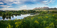 Spring panoramic landscape views of Pineview Reservoir and the surrounding mountains as the sun lights up the bright green hills in Northern Utah.