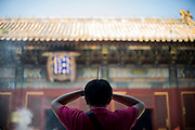A Chinese Buddhist pilgrim prays burning incense at the Yonghe Temple (Chinese 雍和宮, pinyin Yōng hé gōng), also known as the Lama Temple in Beijing, China, August 15, 2014.<br /> <br /> Confucianism, Taoism and Buddhism are the three major religions in China. Temples and statues witness their ancient roots all over the Chinese country.<br /> <br /> © Giorgio Perottino