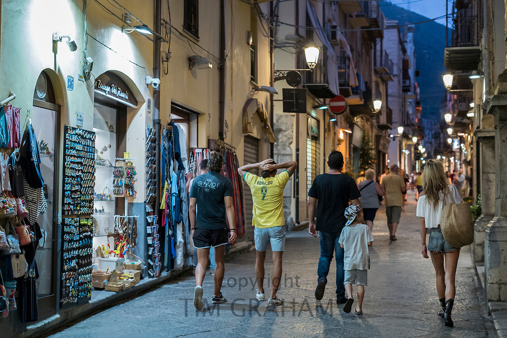 Tourists in street scene and souvenir shops in town of Cefalu in Northern Sicily, Italy