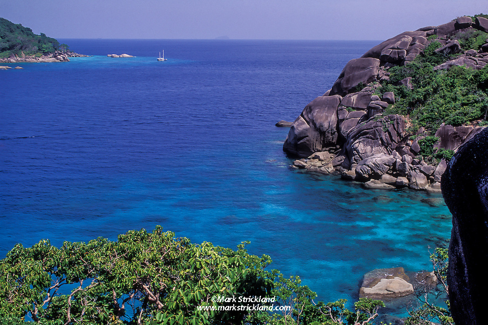 A yacht is moored at Similan Island Number 9, Ko Bangu, seen from Number 8, Ko Similan. Located some 40 miles off Thailand's west coast, the Similans are considered the Jewel of Thailand's Marine National Park system. Similan Islands, Thailand, Andaman Sea.