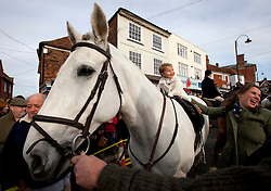 © Licensed to London News Pictures. 26/12/2012. Tenterden, Kent. Alice Chapple, 17 months, granddaughter of the Whip of the hunt sits on  Mac the horse as the townsfolk of Tenterden gather for the Ashford Valley Hunt meet and greet on Boxing Day. Photo credit : Rebecca Mckevitt/LNP
