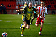 Jason Taylor of Barrow runs to avoid the imminent tackle of Arthur Read of Stevenage during the EFL Sky Bet League 2 match between Stevenage and Barrow at the Lamex Stadium, Stevenage, England on 27 March 2021.
