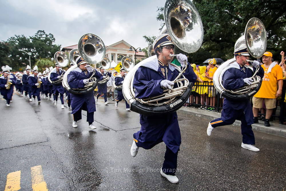 """The LSU Marching Band runs in tempo down Victory HIll while playing the introduction to """"Touchdown for LSU."""" and jogging past thousands of fans lining North Stadium Drive."""
