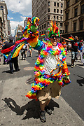 New York, NY - 25 June 2017. New York City Heritage of Pride March filled Fifth Avenue for hours with groups from the LGBT community and it's supporters. A man festooned with colorful floral leis.
