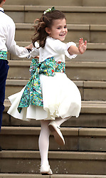 A bridesmaid waves a she arrives for the wedding of Princess Eugenie to Jack Brooksbank at St George's Chapel in Windsor Castle.
