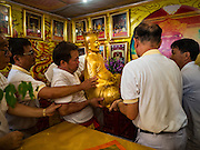 12 OCTOBER 2015 - BANGKOK, THAILAND:   Men carry a statue into a shrine in Chinatown during a ceremony on the first day of the Vegetarian Festival in Bangkok's Chinatown. The Vegetarian Festival is celebrated throughout Thailand. It is the Thai version of the The Nine Emperor Gods Festival, a nine-day Taoist celebration beginning on the eve of 9th lunar month of the Chinese calendar. During a period of nine days, those who are participating in the festival dress all in white and abstain from eating meat, poultry, seafood, and dairy products. Vendors and proprietors of restaurants indicate that vegetarian food is for sale by putting a yellow flag out with Thai characters for meatless written on it in red.     PHOTO BY JACK KURTZ
