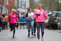 © Licensed to London News Pictures. 13/02/2018. The three hundredth (300) run of the annual Shrove Tuesday Pancake race took place in the centre of Lichfield. The race has run uninterrupted even through both world wars. Pictured the ladies winner Hannah Bull flips her pancake. Photo credit: Dave Warren/LNP