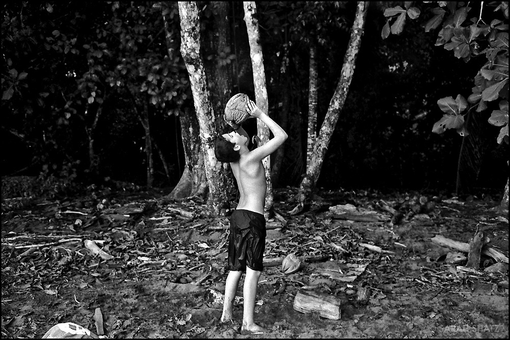 Boy drinking from coconut on the beach