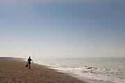 Fisherman walks along Cley Beach, Norfolk, United Kingdom