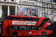 A red London Routemaster bus passes beneath large posters for the Garrick theatre's latest West End play, Twelve Angry Men, on Charing Cross Road. Stopped in traffic, the bus takes passengers on a route through the heart of Theatreland, south towards Trafalgar Square. On the side of the bus is the title of another production, the musical Mormon which is a big hit in the capital. The hybrid NB4L, or the Borismaster, New Routemaster or Boris Bus, is a 21st century replacement of the iconic Routemaster as a bus built specifically for use in London and is said to be 40 per cent more fuel efficient than conventional diesel buses. The brainchild of London's Conservative mayor Boris Johnson, its funding has been controversial amid massive fare increases in transport.