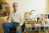 Portrait of man sitting next to cluttered table.