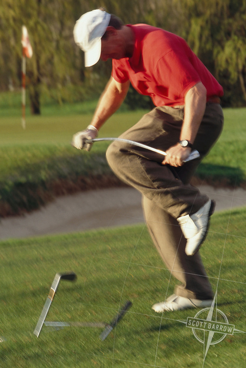 Golfer breaking a club over his