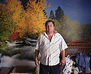 Toma Mihai in his house, in front of a wall mural, in the village of Sintesti, Romania, early August 2006. The Kalderari roma of Sintesti are by tradition metal workers, originally making alcohol stills, pots and pans, but now dealing in scrap metal. The large profits from their business have enabled them to build large houses in the village of Sintesti, 20km from Bucharest, and to invest in fast, Western brand name cars such as BMW's, Mercedes and Porsche.