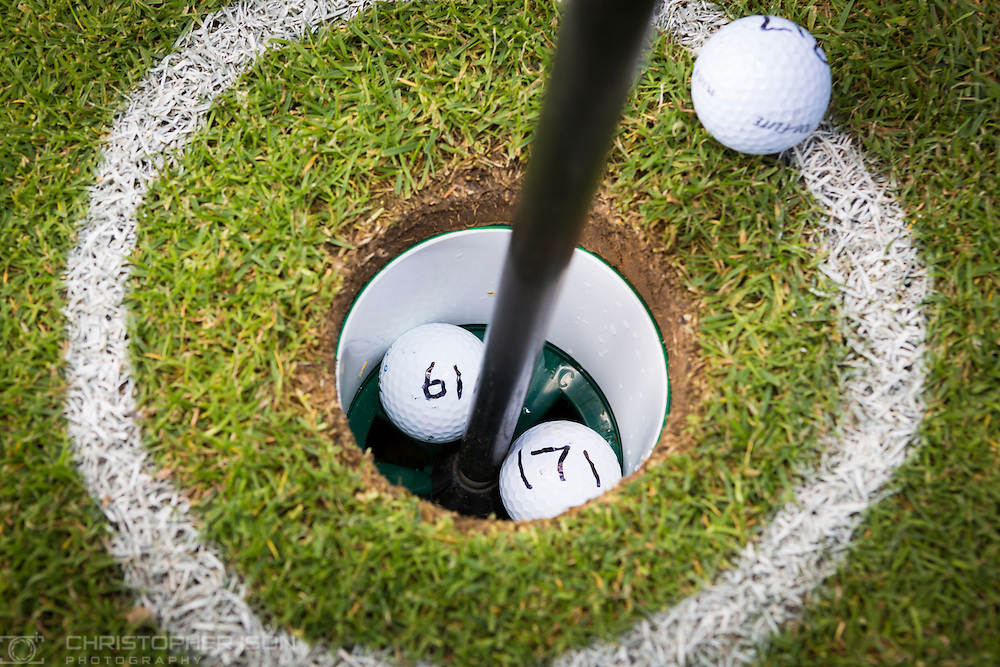140604 ISON Golf Ball Drop<br /> Two balls share the cup after Captain Mike Burns of Atlas Helicopters and colleague Roy Adams dropped 1,000 golf balls from their Squirrel helicopter flying at 90 feet above Cowdray Park Golf Club in Midhurst, West Sussex for charity. The balls had been sold for £5 each with the owner of the ball closest to the hole winning £500. The rest of the money raised was donated to Treloar School and College in Alton, Hampshire, which provides education, care, therapy, medical support and independence training to young people with physical disabilities. Two balls landed in the hole. <br /> Picture date Wednesday 4th June, 2014.<br /> Picture by Christopher Ison. Contact +447544 044177 chris@christopherison.com