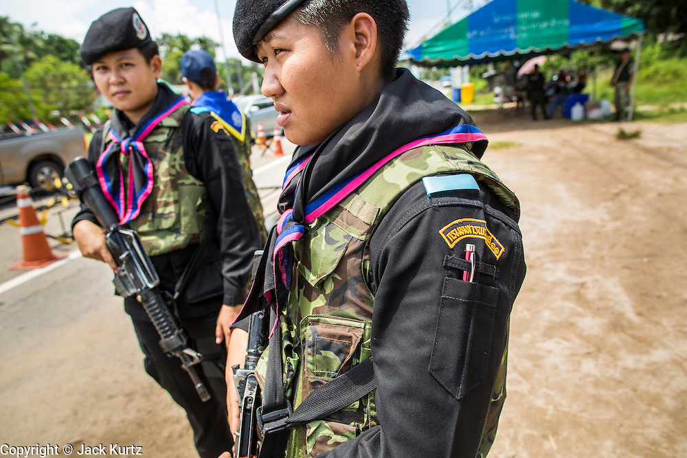 """25 OCTOBER 2012 - TAK BAI, NARATHIWAT, THAILAND: Thai women Rangers (paramilitary operating under Army command) at a checkpoint in Tak Bai, Thailand. The """"Tak Bai Incident"""" took place on Oct. 25 in Tak Bai, Narathiwat, Thailand during the Muslim insurgency in southern Thailand. On that day, a crowd gathered to protest the arrest of local residents. Police made hundreds of arrests during the protest and transported the arrested to Pattani, about two hours away, in another province. They were transported in locked trucks and more than 80 people suffocated en route. This enraged local Muslims and shocked people across Thailand. No one in the Thai army accepted responsibility for the deaths and no one was ever charged. In the past, the anniversary of the incident was marked by protests and bombings. This year it was quiet. More than 5,000 people have been killed and over 9,000 hurt in more than 11,000 incidents, or about 3.5 a day, in Thailand's three southernmost provinces and four districts of Songkhla since the insurgent violence erupted in January 2004, according to Deep South Watch, an independent research organization that monitors violence in Thailand's deep south region that borders Malaysia.   PHOTO BY JACK KURTZ"""