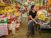 12 OCTOBER 2012 - NAKHON PATHOM, NAKHON PATHOM, THAILAND: A vendor of religious goods waits for customers in the Nakhon Pathom market.   PHOTO BY JACK KURTZ