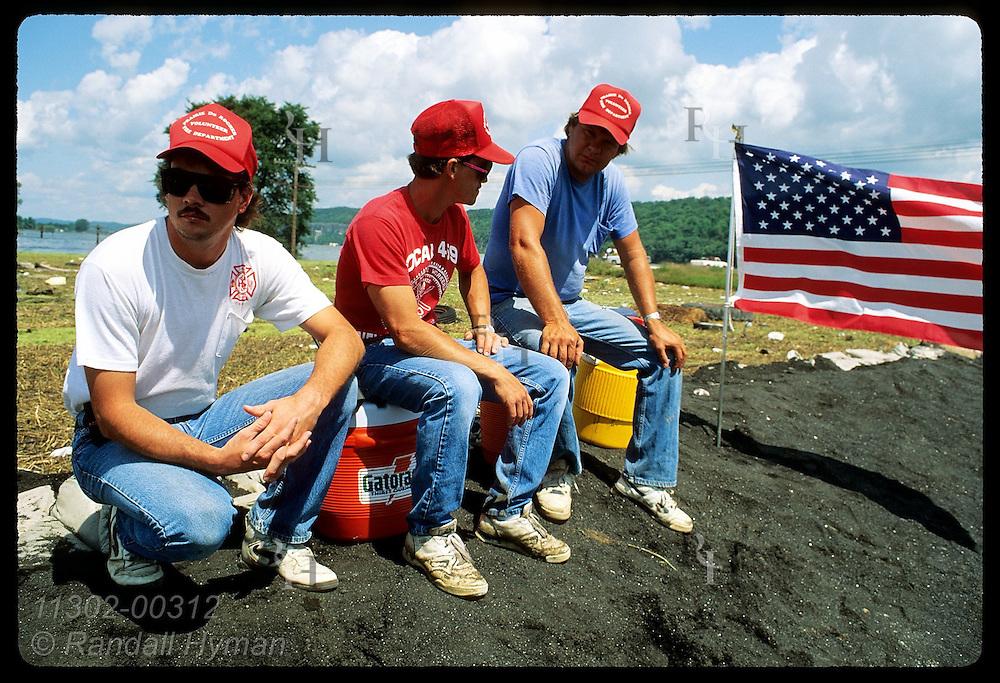 Three sandbaggers sit atop levee beside flag as Mississippi nears top on 8/4/93; Prairie du Rocher Illinois